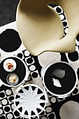 Designer chair and ornaments on side tables on 60s retro-style rug with pattern of black and white circles