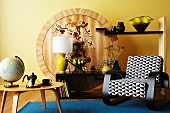 Armchair with black and white upholstery and retro table in front of unusual shelving with painted wooden back wall