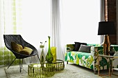 Flower power sofa, retro wicker chair and vases arranged on round side tables