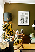 Elegant armchair with animal print cover, Oriental china figurines and orchid in silver pot below framed drawing