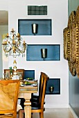 Elegant dining area with crystal candelabra on antique table; silver beakers in blue-painted niches