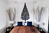 Bedroom in natural design with tall bundles of twigs behind bedside tables and wall hanging with picture of stylised tree