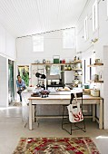 Bright, spacious kitchen with vintage furniture, rustic kitchen shelves and antique cooker below sloping, corrugated metal ceiling