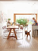 Delicate, chrome-framed chairs at wooden table opposite woman working at kitchen counter in modern interior with open terrace doors