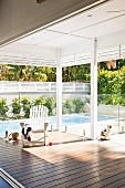 Roofed veranda with view of swimming pool
