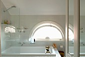 Bath and shower with glass screen in front of semi-circular window in bathroom