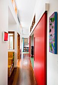 Corridor with red sliding doors and various transom window elements leading between open-plan rooms