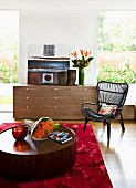 Interior with walnut-veneer chest of drawers & round coffee table