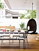 Hanging chair, table, chairs and bench on deck-style roofed terrace