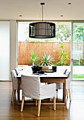 Dining table, armchairs with loose covers & pendant lamp in front of open sliding doors leading to garden