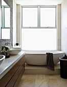 Bathroom with washstand and oval free-standing bathtub on platform in front of floor-to-ceiling sash window