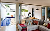 Living room with corner sofa & open folding doors leading to deck-style terrace with pool