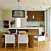 Open-plan kitchen with walnut veneer, dining table and chairs with loose covers