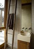Wooden ladder next to a bathroom vanity under a mirror