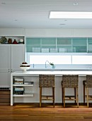White fitted kitchen with modern fronts, vintage cupboard and wicker chairs at kitchen counter