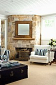 Rustic, rough stone wall with open fireplace and square mirror on chimney breast in living room with Hamptons-style furniture; books on vintage trunk in foreground