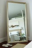 Full-length, silver-framed mirror in elegant bedroom with striped bed headboard and modern painting