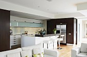 View across white sofa set into designer kitchen with white, central island; fitted cupboards with wooden doors