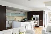 Blick über weisse Sofagarnitur auf Designer Küche mit Mittelblock in Weiss; Einbauschränke mit Holzfronten