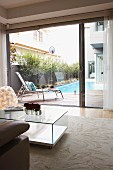 Cubic, glass coffee table on pale rug in front of open sliding door and view across terrace to pool in courtyard
