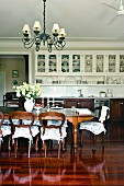 Antique style dining room with long dining table and romantic chair cushions on wooden chairs in an open living room with a stately, built-in kitchen