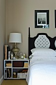 Nightstand with books and elegant table lamp next to a double bed with a black and white headboard
