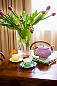 Bouquet of purple tulips in glass vase and gold-rimmed tea set on antique wooden table