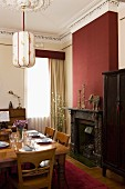 Set dining table and open fireplace in burgundy chimney breast in grand dining room with stucco ceiling