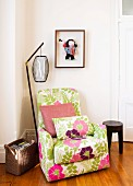 Comfortable armchair with cheerful floral upholstery and retro standard lamp in corner