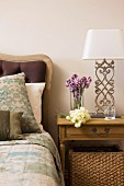 Wooden bedside table and table lamp with white lampshade and metal base next to bed with upholstered headboard