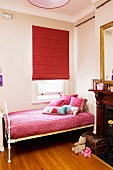Girl's bedroom with antique, white metal bed frame below window with closed, red Roman blind and open fireplace in traditional interior