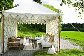Benches and delicate side tables in tent-like pavilion of floral fabric in green landscape