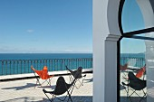 Butterfly chairs in various colours on terrace beneath blue sky with sea view over metal balustrade