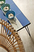 Backrest of wicker chair and blue tiled side table