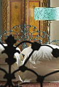 Bed with floral, metal frame in front of standard lamp with turquoise lampshade and painted wardrobe