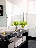 Bouquet of yellow tulips on marble washstand with towels on shelf and retro tap fittings; floor-level shower in background
