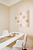 Dining table and white shell chairs in front of modern artwork on beige-painted wall