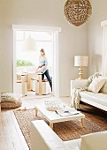 White, low coffee table on sisal rug and pale sofa set opposite open doorway showing view of woman setting table
