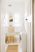 View through open door of modern wooden stool next to toilet below window in white-tiled bathroom