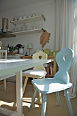 Pastel farmhouse chairs around white-painted dining table in bright, simple kitchen
