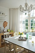 Sunny, simple kitchen with bay window, square dining table and vintage chairs; crystal chandelier above table