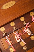 Forged keys with red and white gingham ribbons on key rack with numbered brass plates