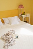 Double bed with yellow headboard and white bed linen in bedroom with yellow walls