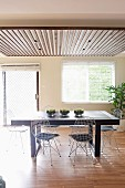 Sonniger Essplatz mit schwarzem Tisch und gepolsterten Drahtstühlen unter abgehängter Decke