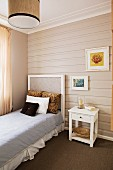 Horizontal wood cladding on wall behind single bed and white, nostalgic bedside table
