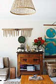 View across coffee table to rustic cupboard and disused wooden rake on wall