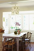 Simple wooden table and classic chairs below pendant lamp with paper lampshade in wood-panelled bay window