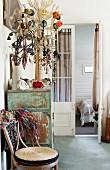 Thonet chair next to jewellery rack on vintage cabinet in front of open bedroom door