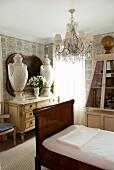 Antikes Bett mit dunklem Holzgestell und Antiquitäten im Gästezimmer