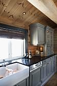 Hellgrau lackierte Holzfront an Unterschränken und Hängeschränken einer Landhausküche im Holzhaus